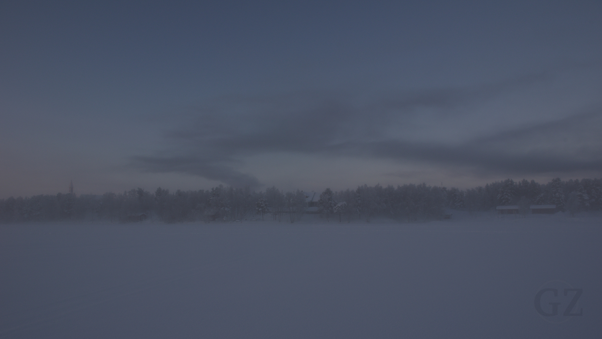 Silhouette of village in fog, seen from a frozen lake