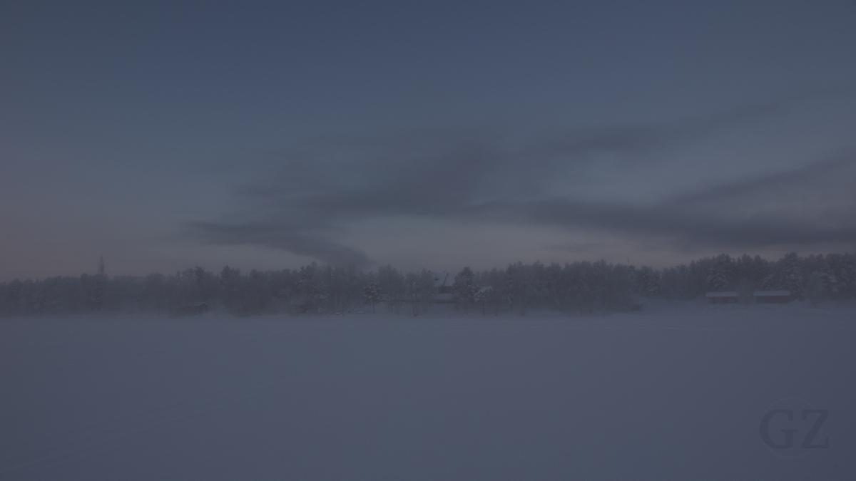 Silhouette of village in fog, seen from a frozen lake